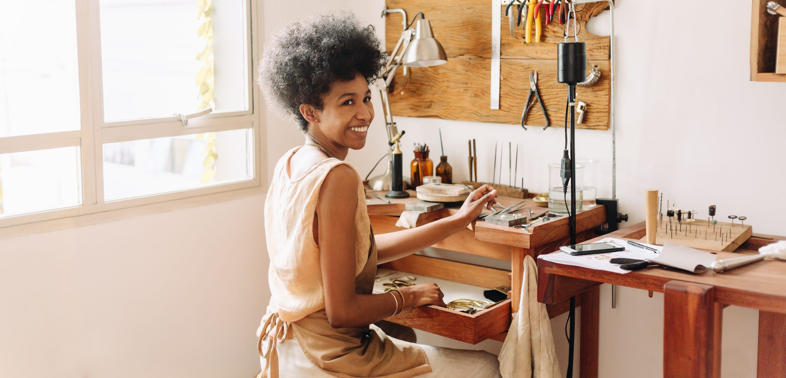 African,Artist,Glancing,Back,While,Working,At,Jewelry,Workshop.,Cheerful